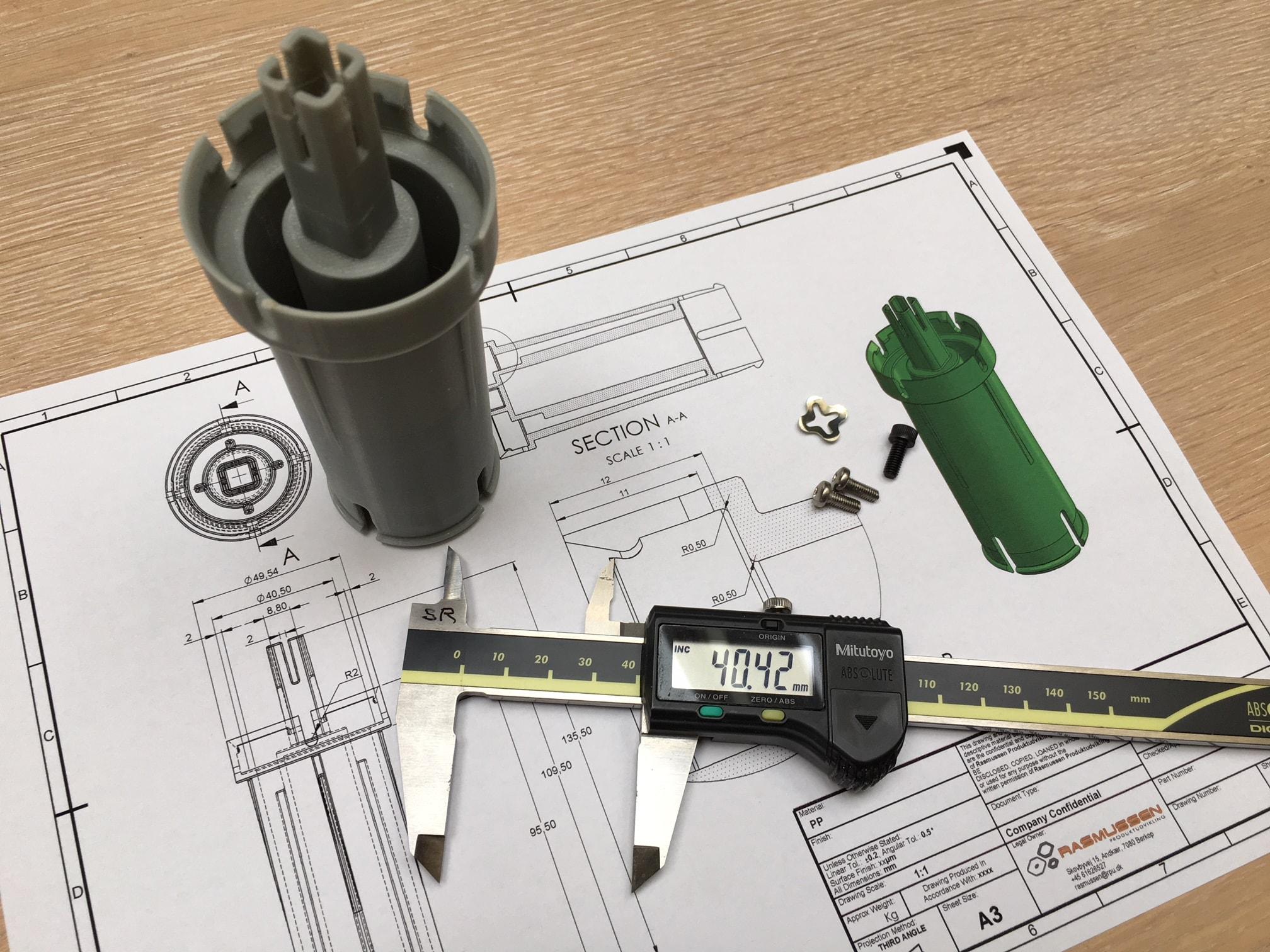 3D printet prototype vist fysisk sammen med 2D tegningen under